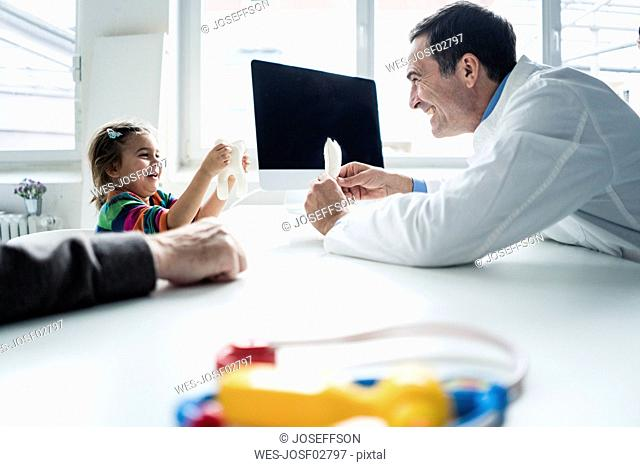 Doctor and happy girl with tooth model at desk in medical practice