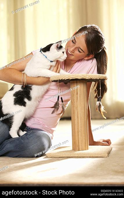 Portrait of teenage caucasian girl sitting on rug in living room showing new scratching post to her pet cat