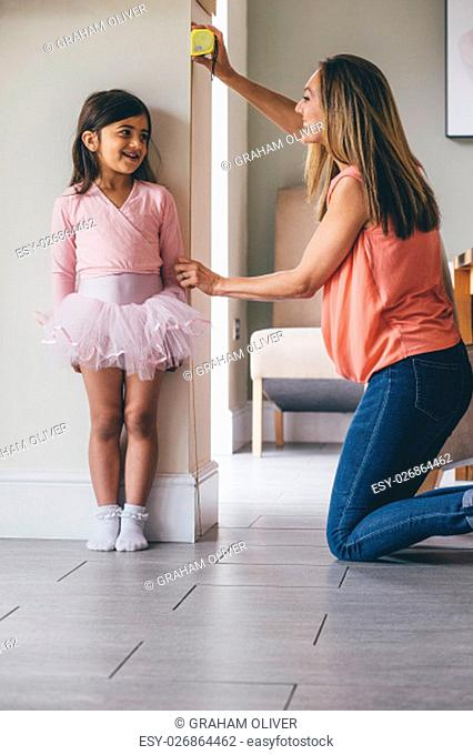 Little girl in a ballet costume having her height measure by her mother. She is standing against the wall whilst her mother uses the tape measure