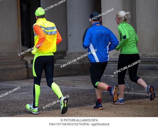 06 November 2019, Brandenburg, Potsdam: Three joggers run past the Orangerie in Sanssouci Park. Photo: Monika Skolimowska/dpa-Zentralbild/dpa