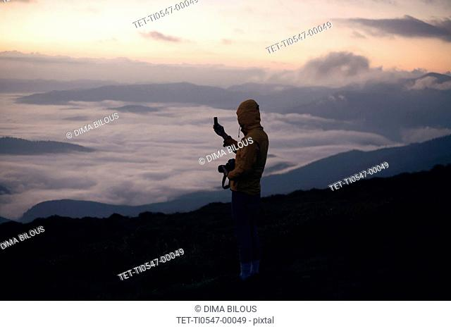 Young man photographing with smart phone at sunset in the Carpathian Mountain Range