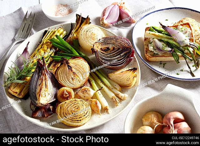 Plates and dishes with a variety of roasted onions, a selection of onions on toast and uncooked shallots in a bowl