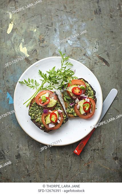Toast with a herb sauce, tomatoes, cucumber and chilli