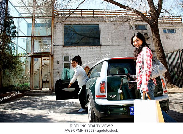A woman and man getting off car in front of the studio