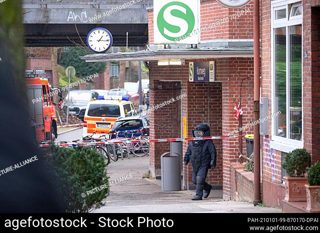 01 January 2021, Hamburg: The defuser comes out of the station entrance in an armoured protective suit. On New Year's Eve