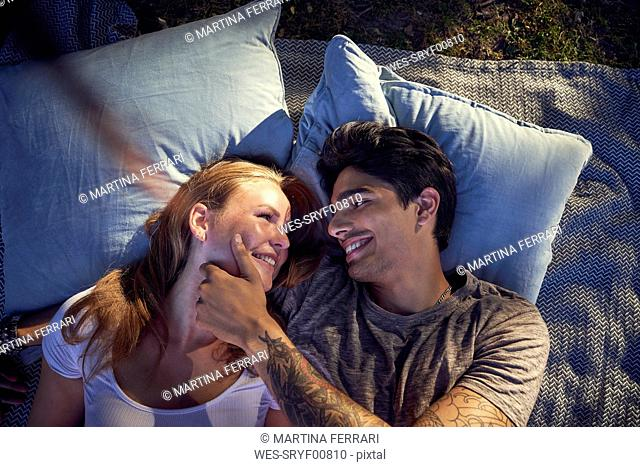 Young couple in love, lying on cushions