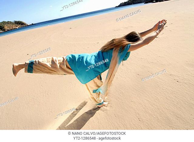 Yoga teacher and artist Lena Tancredi, doing yoga on a peaceful beach of Ibiza, Spain
