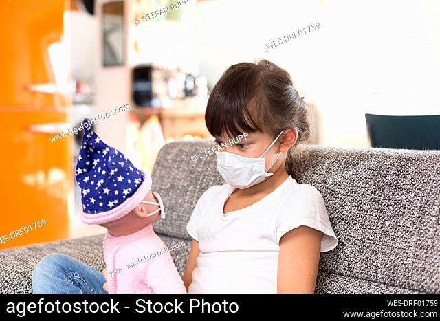 Little girl with protective mask sitting on couch at home playing with doll