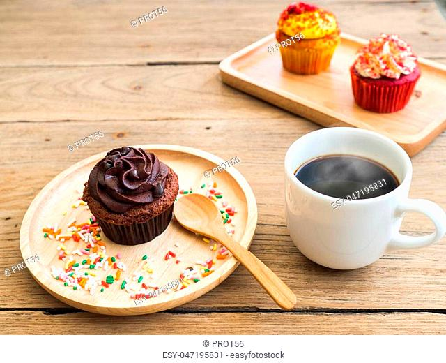 chocolate cupcake put on a spherical wooden plate. Beside of cupcake have Vintage alarm clock and white coffee mug.In the background have yellow cupcake and Red...