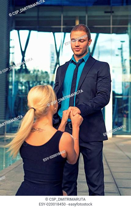 Woman standing on one knee and making proposal to man