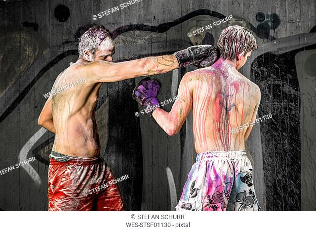 Two boxers covered with paint fighting