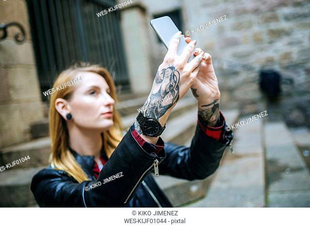Tattooed woman's hands taking selfie with cell phone