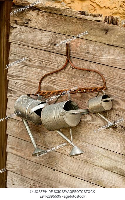 The outside of an old garden shed with antique watering cans hanging on the wall.Georgia USA