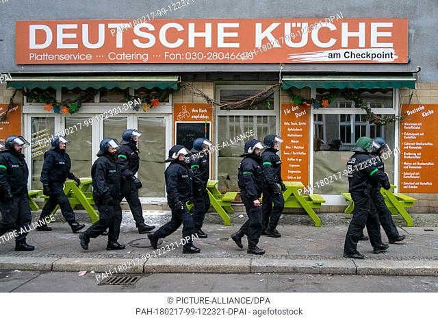 dpatop - Police officers walk üast a restaurant at the Friedrichstrasse reading 'Deutsche Kueche' (lit. German cuisine) prior to a 'women's march' coming from...
