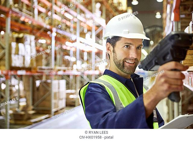 Worker using scanner in distribution warehouse