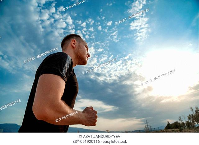 portrait of a young Caucasian guy in a black t-shirt and black shorts running at sunset