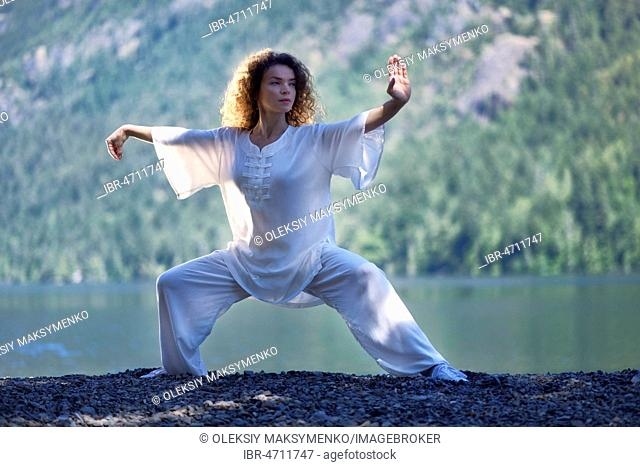 Young woman in white outfit practicing a Tai Chi, Taiji, Ban Ma Bu stance by the lake in the nature
