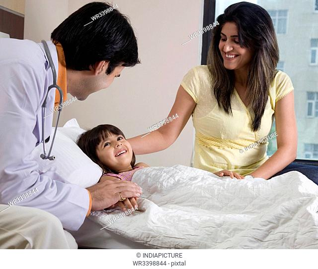 Doctor sitting with a little girl and her mother