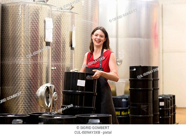 Portrait of young woman in wine cellar next to fermentation tanks, smiling