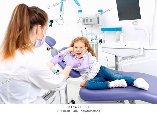 Adorable little girl smiling and looking at camera sitting in dentist chair while dental specialist preparing tools for treatment in a clinic