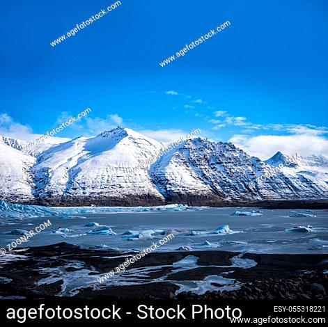 Huge majestic glacier's icy surface by snowy mountain in Iceland