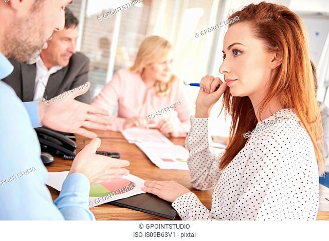 Colleagues having discussion in business meeting