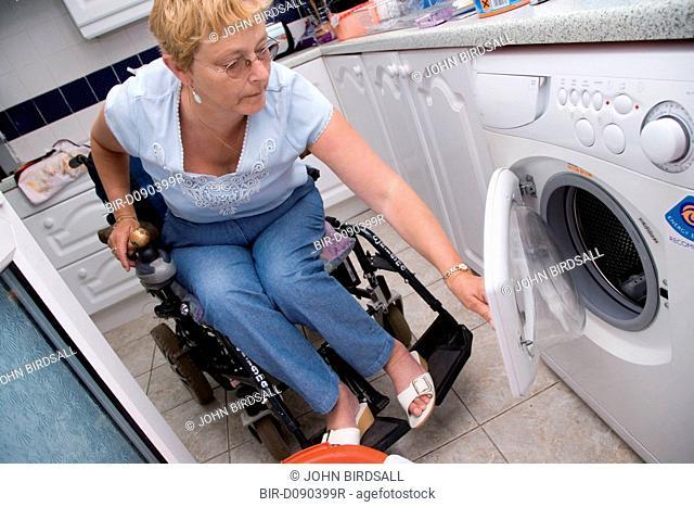 Woman wheelchair user loading the washing machine