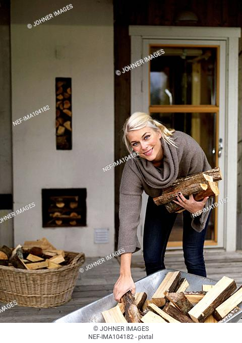 Smiling woman picking firewood