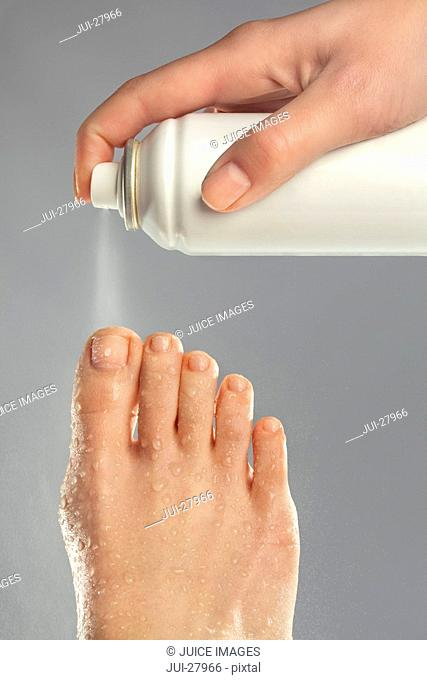 A woman spraying cooling spray onto her foot