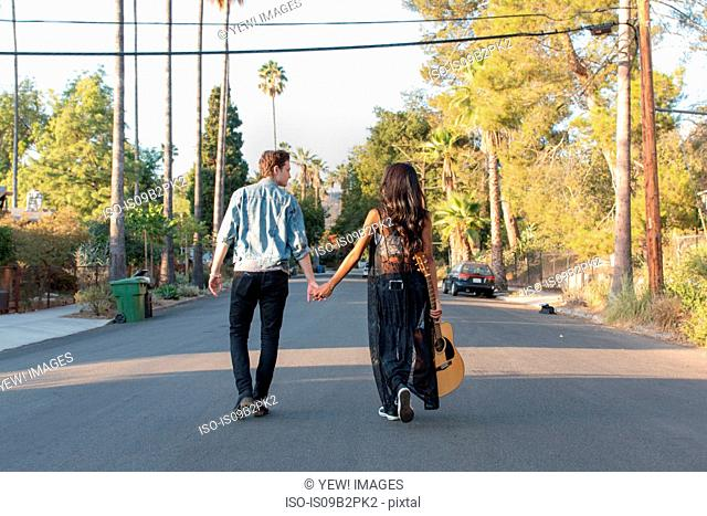 Young couple walking outdoors, young woman holding guitar, rear view