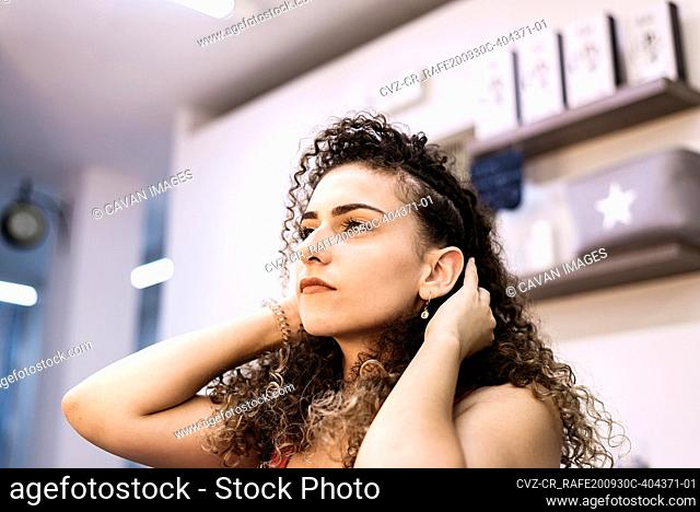 Portrait of woman combing with hands at hairdresser salon