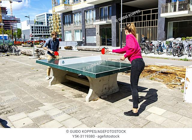 Amsterdam, Netherlands. The freelance working colleagues play a little game of pingpong, just outside their office building