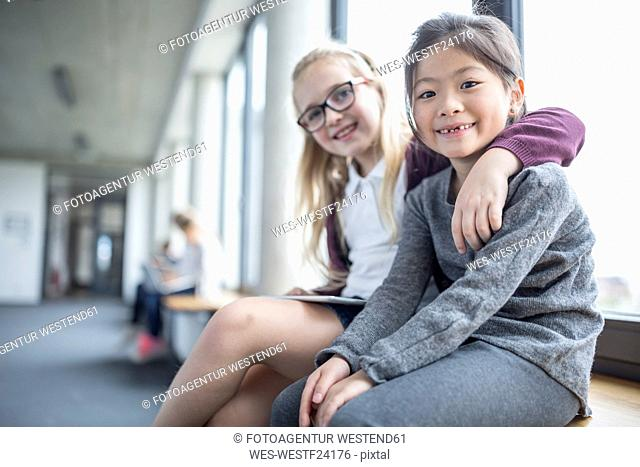 Portrait of two smiling schoolgirls sitting on school corridor
