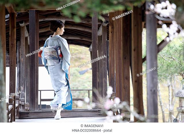 Young Japanese woman in kimono with parcel walking on wooden bridge