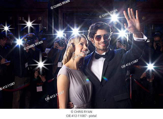 Well dressed celebrity couple waving to paparazzi at red carpet event