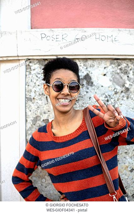 Portrait of smiling young woman wearing sunglasses and striped pullover showing victory sign