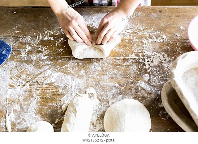 Baker's hands kneading dough at table in bakery
