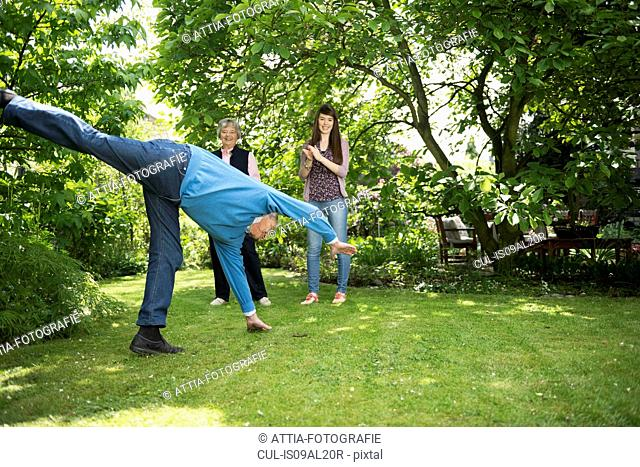 Grandparents and granddaughter doing acrobatics in garden
