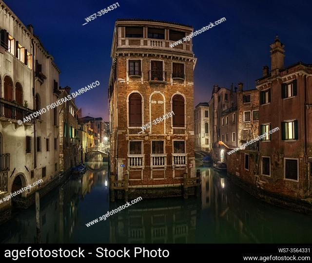 A Venice house between canals at sunrise