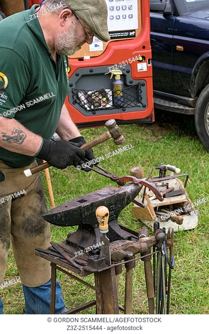 A farrier shaping a horseshoe at the Essex Country Show, Barleylands, Essex