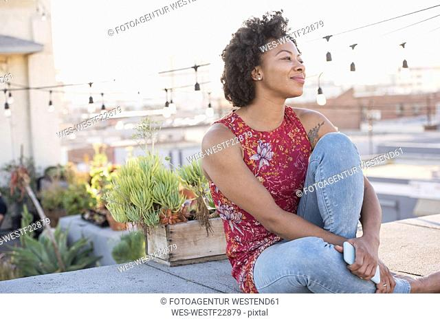 Young woman sitting on rooftop terrace, enjoying the sun