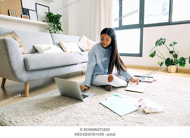 Young woman sitting on floor in the living room usinf laptop