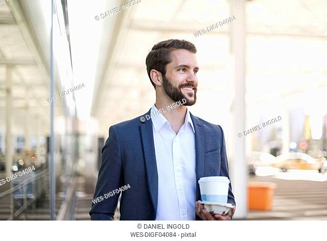 Smiling young businessman holding tray with takeaway coffee