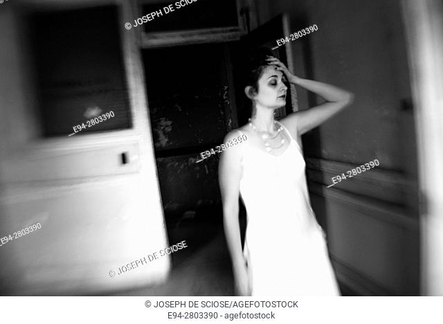 A 25 year old woman with hand on her head wearing a white dress walking through a doorway in an abandoned office building