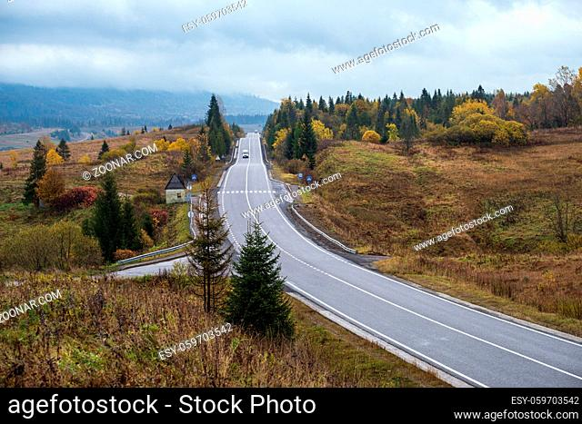 Hazy and overcast Carpathian Mountains and highway on mountain pass, Ukraine