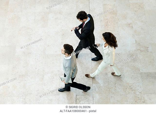 Business people walking through office lobby