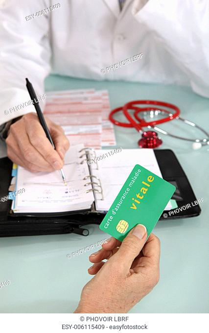 Patient handing social security card to doctor