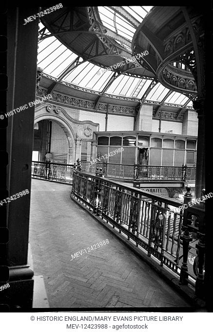 An interior view of City Markets, seen from a balcony on a short side of the hall, showing an internal gateway to another section of the market with a wooden...