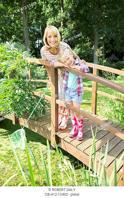 Grandmother and granddaughter smiling on wooden footbridge