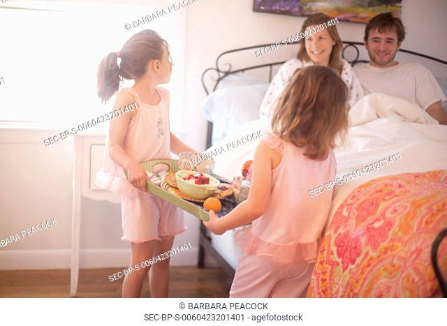 Two girls (4-5, 6-7) serving breakfast to their parents sitting in bed
